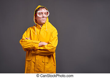 Man in yellow raincoat - A serious middle aged man standing...