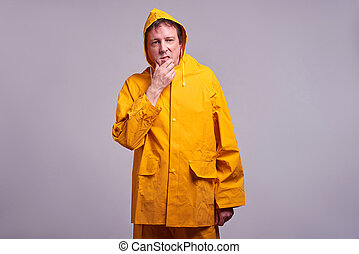 Man in yellow raincoat - A middle aged man standing and...