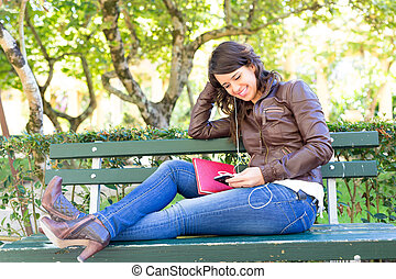 Finally ! A day off! - Young woman listening to music at the...
