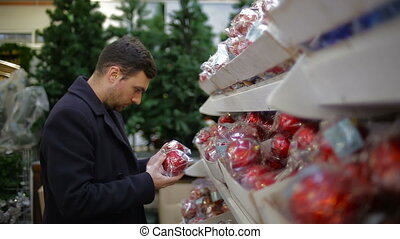 Man chooses Christmas decorations in a shop