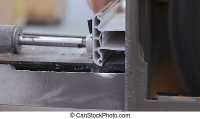 The factory machine cutting PVC profile with circular saw.