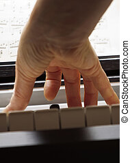 Piano keyboard made of ivory with hands - Close-up of...