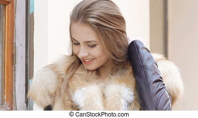 Cute girl posing in furry jacket on the street. Slow motion.