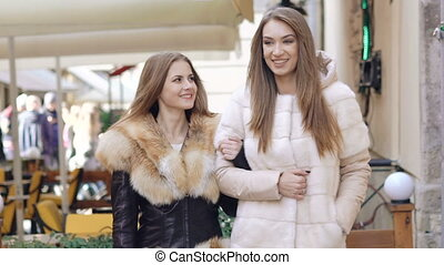 Two glamour girls walking in furry coats in shopping center....