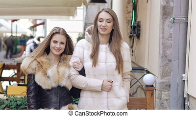 Two happy girls walking in furry coats in shopping center....