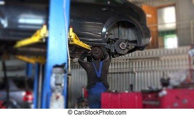 car mechanic worker repair suspension of lifted automobile at repair garage.