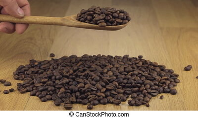 Coffee beans get enough sleep from a wooden spoon on a pile...