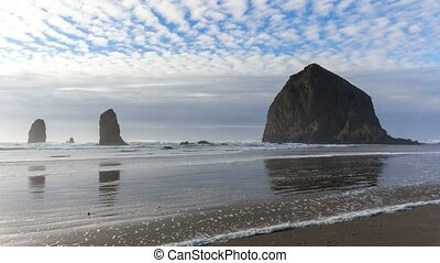 Time lapse of clouds and sky over Haystack Rock at low tide along Pacific Ocean in Cannon Beach OR 4k