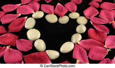 Drops of water falling into the heart made of stones and rose petals