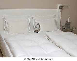 Clock on Pillows on a Bed - Bed with pillows, bedclothes and...