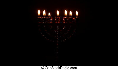 Menorah in the dark - Golden Menorah with seven pin shines...