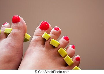 Painting toenails at home - womans feet with fresh red nail...