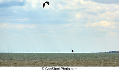 Athletic man jump on kite surf board on a sea waves.