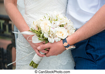 Hands newlyweds with a bouquet. A newly weding couple place...