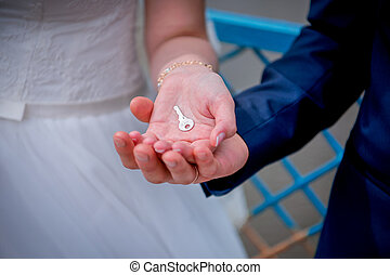 Key in the hands of the newlyweds - Hands newlyweds with a...