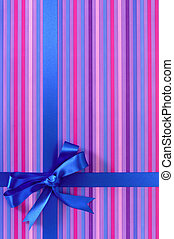 Blue gift ribbon bow on candy stripe wrapping paper...