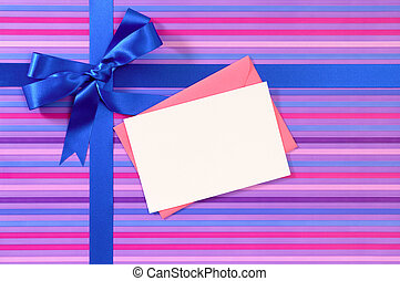 Blue gift ribbon bow on candy stripe wrapping paper, blank...