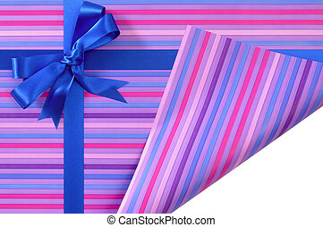 Blue gift ribbon bow on candy stripe wrapping paper, corner...