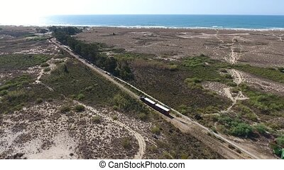 Aerial. Train goes through the Ria Formosa to the beach...