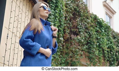 Fashionable girl looking aside in blue coat on the street...