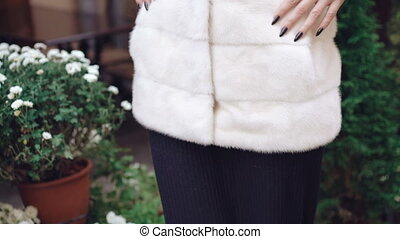 Stylish girl posing to camera in fur coat on the street 4K.