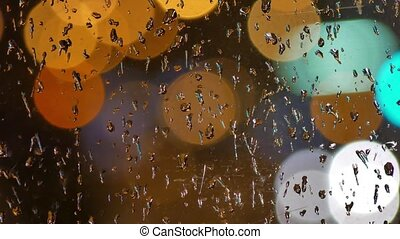 Defocused night traffic lights Through the glass in drops of...