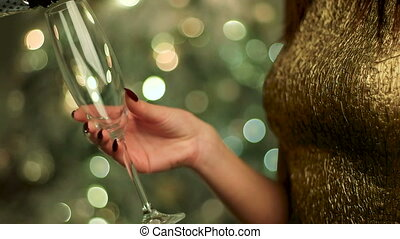 Woman in gold dress holding a glass of champagne sparkle on New Year Eve.