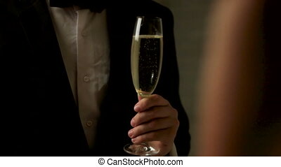 Close up of young man wearing classical suit with a glass of champagne on his hands.