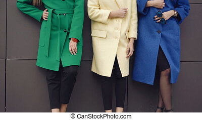 Three fashionable models posing to camera in coats near the wall 4K