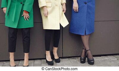 Three stylish models posing to camera in coats near the wall...