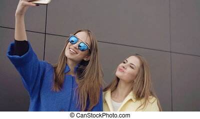 Two fashionable girls taking selfie in the coats and sunglasses 4K