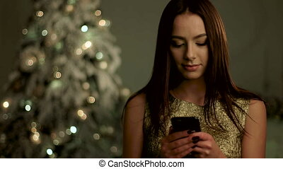 Beautiful young woman with professional make up , talking on mobile phone near Christmas tree.