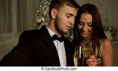 Beautiful woman and her handsome boyfriend taking selfies on New Year day.