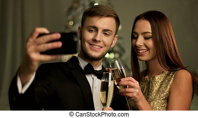 Happy couple taking selfies on New year day, holding on hands two glasses of champagne.