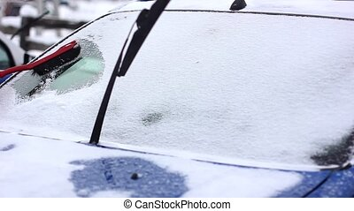 clean the windshield from snow - Owner cleans his car from...