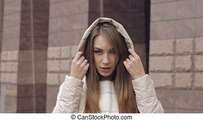 Pretty woman looking on the camera and wearing the hood in...