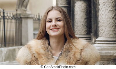 Cute girl posing in furry jacket on the street and smiling...
