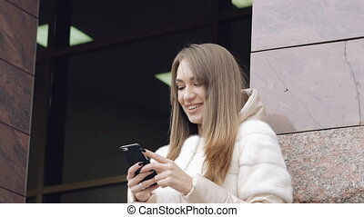 Pretty girl using phone near the office outdoor in full HD