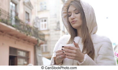 Pretty girl drinking a cup of coffee on the street, enjoying...