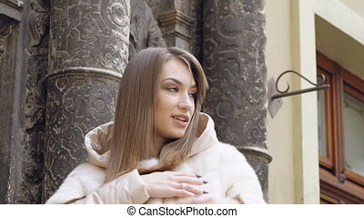 Fashionable girl posing in furry coat on the street in full...