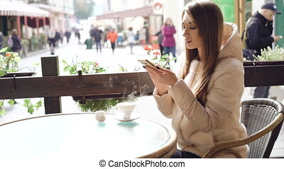 Pretty girl using phone in cafe when coffee is steaming 4K.
