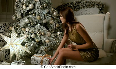 Attractive young woman wearing gold dress, sitting near Christmas tree and opening a box with gift.