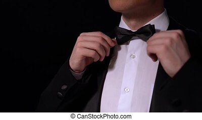 View of conductor straightens his bow tie, close-up