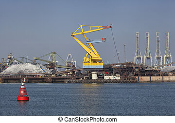 Port cargo crane and sand over blue sky background