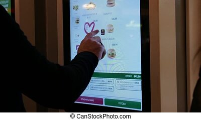 A person uses the touchscreen menu for odering some food in...