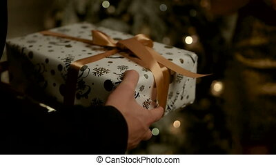 Happy handsome man gifting a gift in white and gold colored box for his beautiful lady.