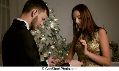 Happy young man gifting handmade gift for his beautiful girlfriend.