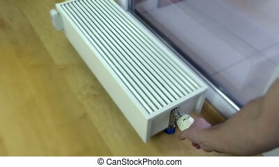 Person's Hand Adjusting Temperature Of Radiator Thermostat....