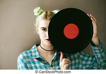 a woman with the disc. young beautiful hipster girl with old...