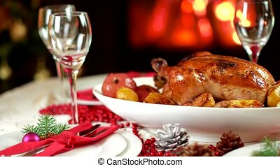 roasted chicken on christmas table in front of fireplace and...
